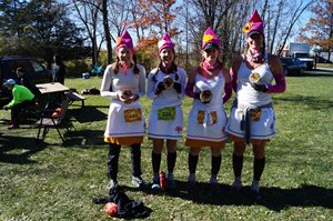 Four runners dresses as gnomes holding finishers plaques