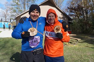 Two male finishers holding branded finishers wood plaque.